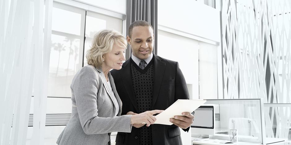 Man and woman reading document   Atradius Takaukset